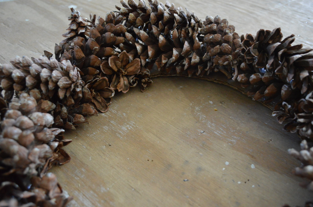 Hot gluing pinecones to fall wreath 3