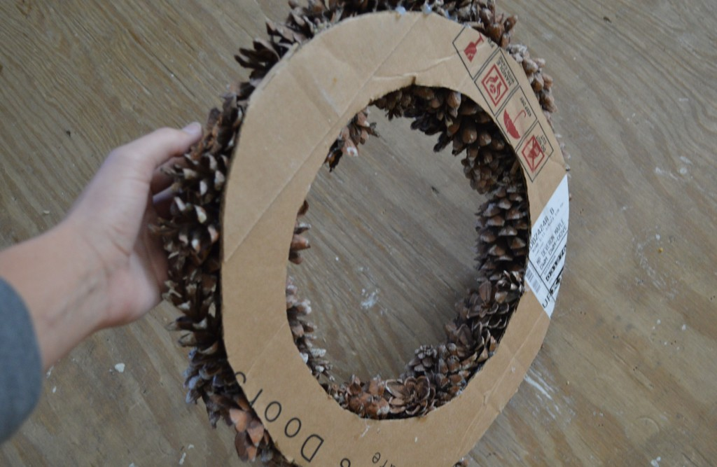 Hot gluing pinecones to fall wreath 5