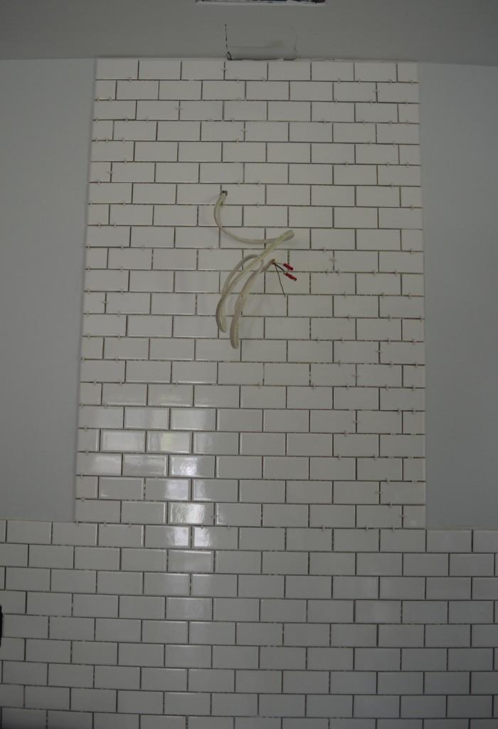 Tiled backsplash done before grout behind range hood