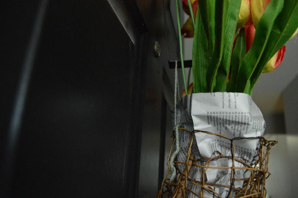 DIY Newsprint Wrapped Tulip Wreath for Front Door adding leaves hanging on door