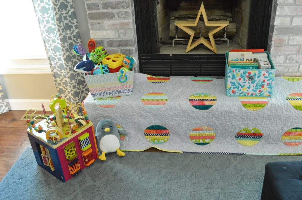 Toys and quilt on brick hearth babyproofing