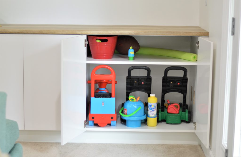 Outdoor toys in basement built in cabinets